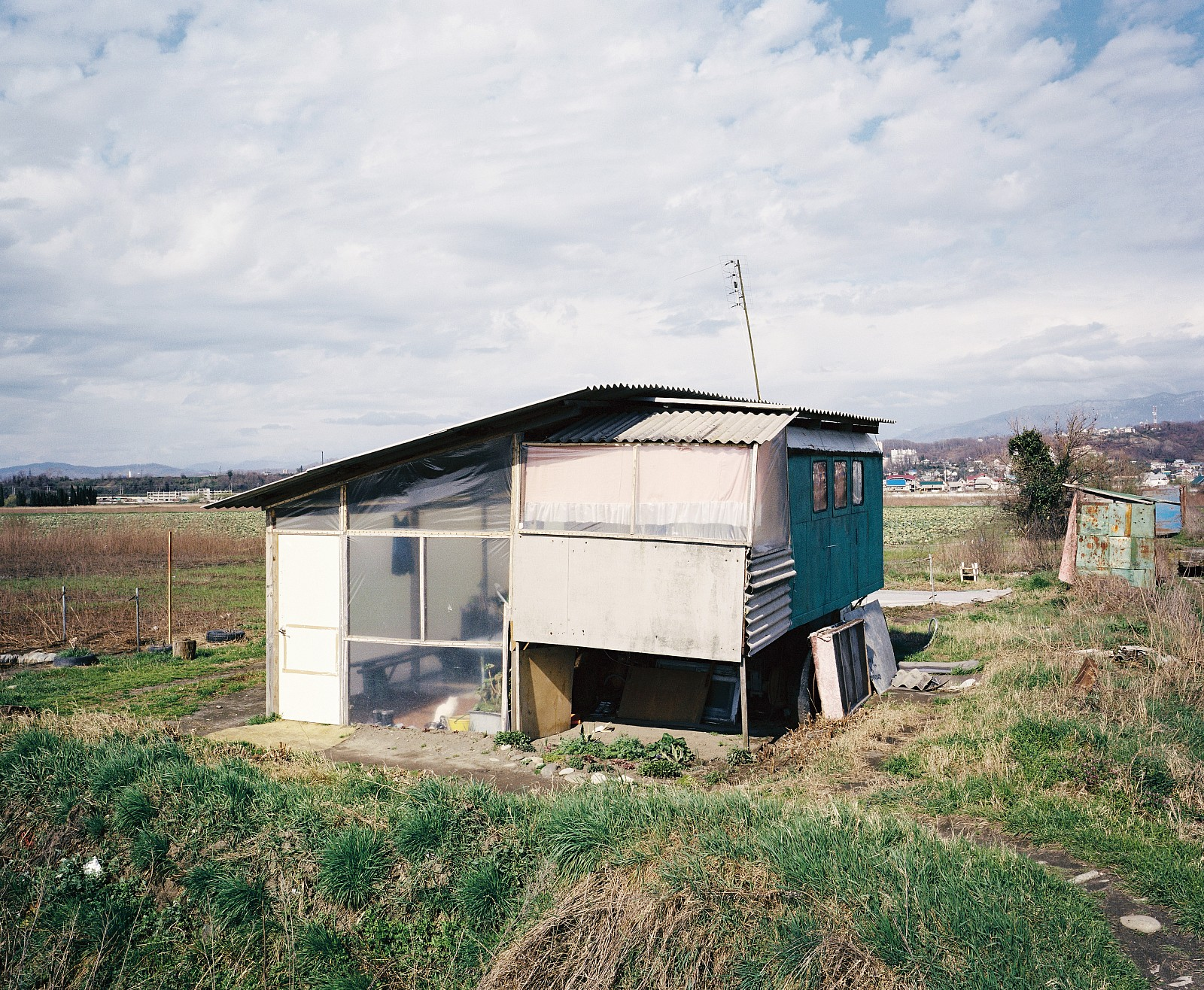 In 2009, state farm 'Russia' was fenced off with a big blue, Olympic fence. Refugees from Abkhazia were allowed to temporarily farm the land. They lived in this caravan.
